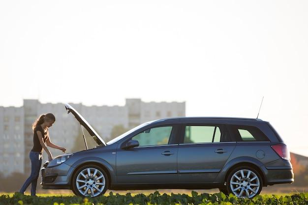 Giovane donna attraente che controlla il livello dell'olio nel motore di un'auto con il cofano spuntato utilizzando l'astina di livello sullo spazio della copia del cielo sereno. trasporto, problemi di veicoli e concetto di guasti. Foto Premium