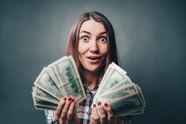 Giovane donna attraente che mostra emozioni sincere di eccitazione e felicità con le banconote in dollari nelle mani Foto Premium