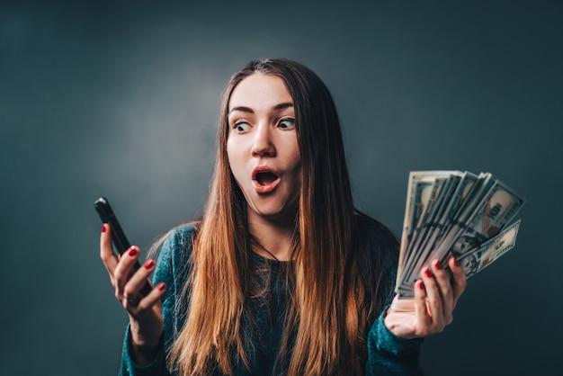 Giovane donna attraente che mostra sincera eccitazione per la vittoria nella lotteria in linea Foto Premium
