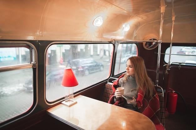 La giovane donna attraente che si siede al tavolo nel bar dell'autobus è coperta da una coperta, tiene una tazza di caffè nelle sue mani e guarda nella finestra Foto Premium