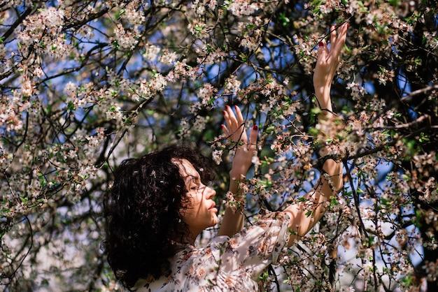 Giovane donna attraente con capelli lunghi ricci in posa nel giardino fiorito primaverile Foto Premium
