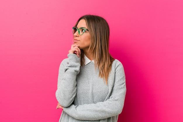 Giovane autentica carismatica gente vera donna sul muro guardando lateralmente con espressione dubbiosa e scettica. Foto Premium
