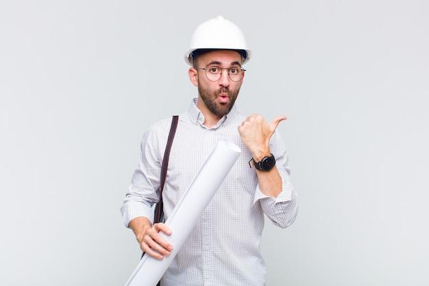 Giovane uomo calvo che guarda stupito incredulo, indicando un oggetto sul lato e dicendo wow, incredibile Foto Premium