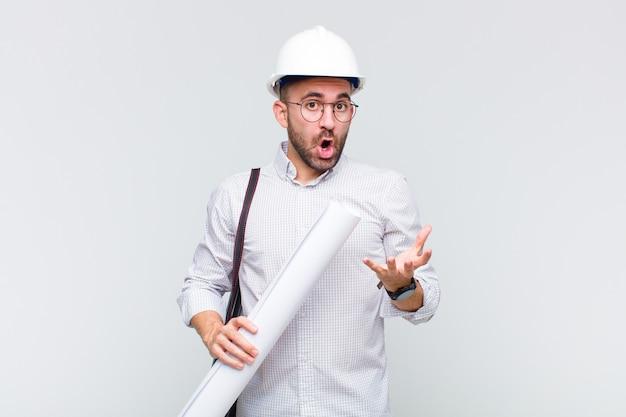 Giovane uomo calvo a bocca aperta e stupito, scioccato e sbalordito da un'incredibile sorpresa Foto Premium