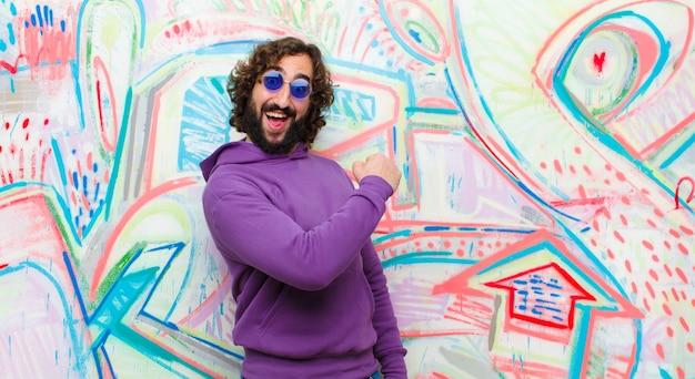 Giovane barbuto pazzo che si sente felice, positivo e di successo, motivato di fronte a una sfida o a celebrare buoni risultati contro il muro dei graffiti Foto Premium