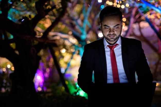Giovane imprenditore indiano barbuto contro la vista della città di notte Foto Premium