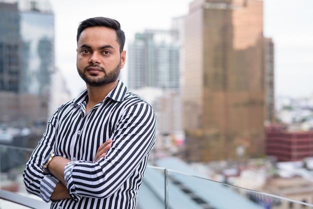 Giovane uomo d'affari indiano barbuto contro la vista della città Foto Premium