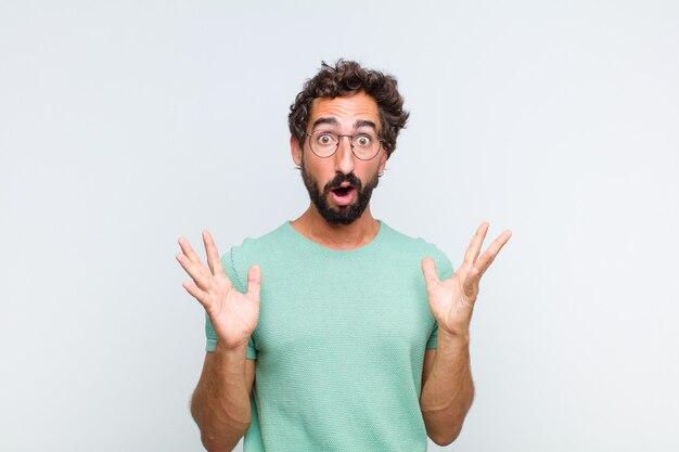 Giovane uomo con la barba che sembra scioccato e stupito, con la bocca aperta per la sorpresa quando realizza qualcosa di incredibile Foto Premium