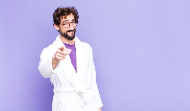 Giovane uomo barbuto che indossa accappatoio che punta con un sorriso soddisfatto, fiducioso, amichevole, scegliendo te Foto Premium