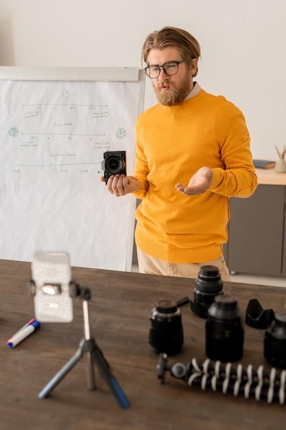 Giovane uomo barbuto con la fotocamera che spiega come scattare foto di stock al suo pubblico online davanti alla fotocamera dello smartphone Foto Premium