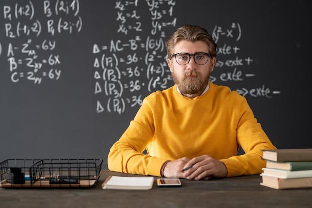 Giovane barbuto insegnante di algebra seduto a tavola sulla lavagna con formule ed equazioni durante la lezione online in aula Foto Premium