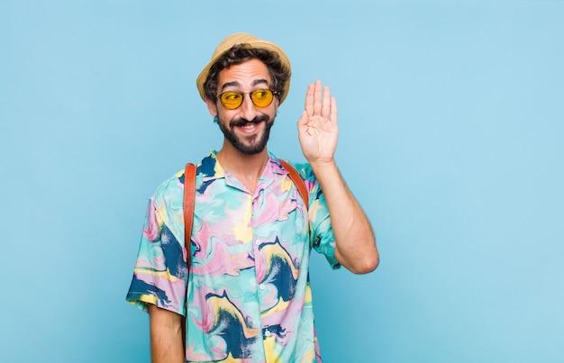 Giovane turista barbuto sorridente, guardando curiosamente di lato, cercando di ascoltare i pettegolezzi o di sentire un segreto Foto Premium