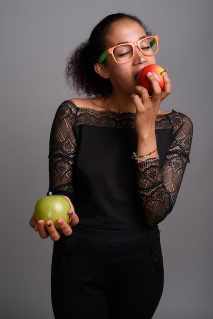 Giovane bella donna africana su grigio Foto Premium