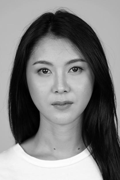 Giovane bella donna asiatica isolata in bianco e nero Foto Premium