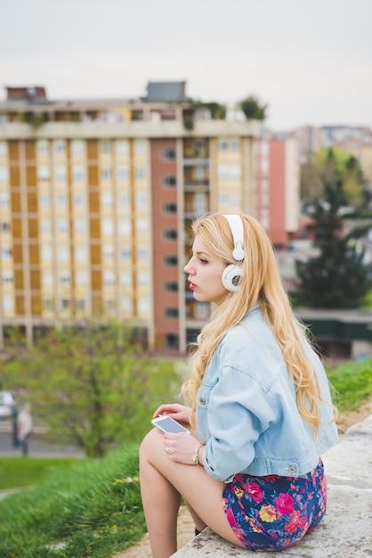 Musica d'ascolto della giovane bella ragazza caucasica bionda Foto Premium