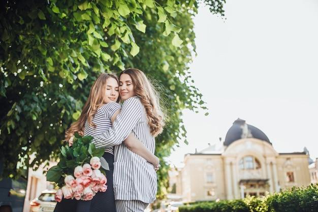 Giovane e bella figlia bionda abbraccia la sua mamma di mezza età per le strade della città. Foto Premium