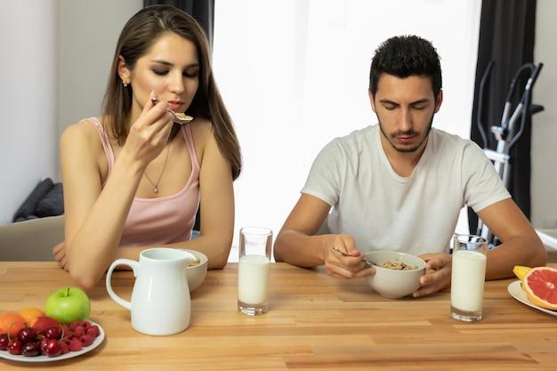 La giovane bella coppia mangia il cereale da prima colazione con le bacche e il latte. Foto Premium