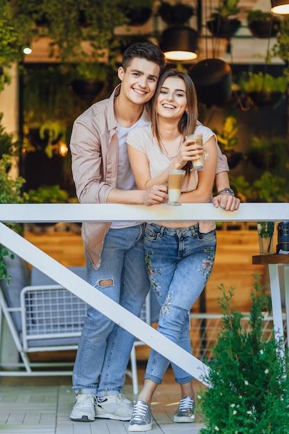 Giovani belle coppie che abbracciano sulla terrazza estiva del ristorante in abiti casual con latte nelle loro mani Foto Premium