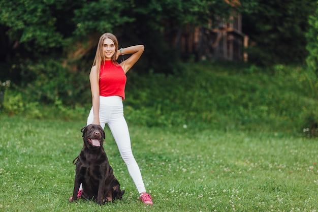 Giovane bella ragazza con il suo cane nero labrador nel parco. Foto Premium
