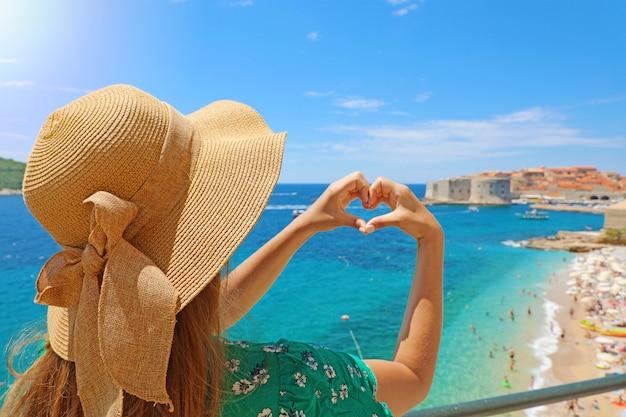 Giovane bella donna a dubrovnik che fa le mani a forma di cuore in primavera estate calda giornata di sole. ragazza con cappello all'aperto felice nel suo viaggio nel sud della croazia, europa. Foto Premium