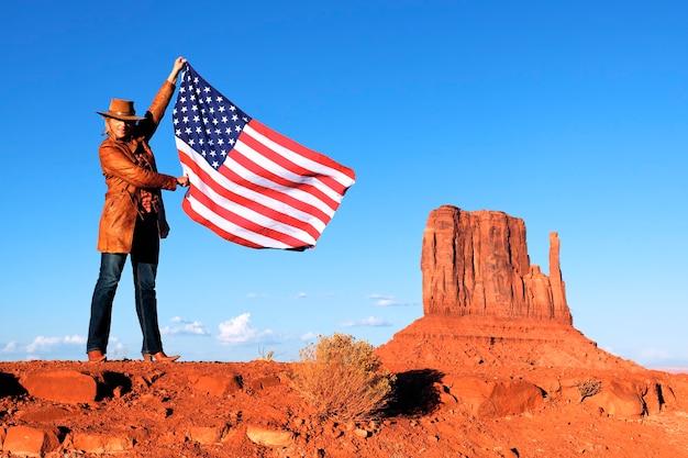 Giovane bella donna che tiene la bandiera usa alla monument valley Foto Premium