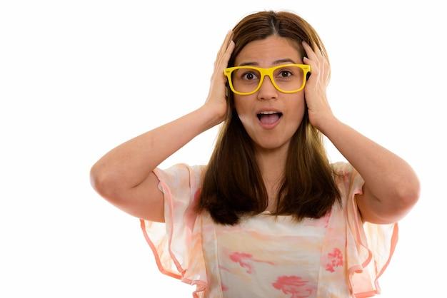 Giovane bella donna che sembra scioccata con entrambe le mani sulla testa Foto Premium