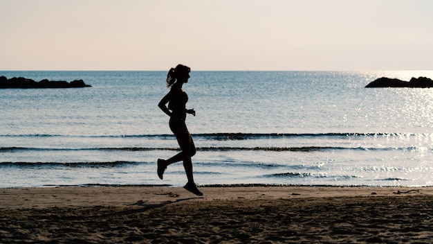 Giovane bello ritratto della siluetta della donna che corre all'aperto sulla spiaggia. Foto Premium