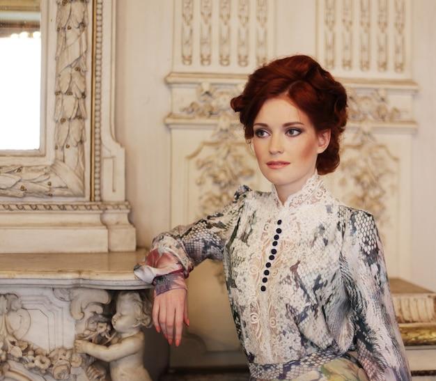 Giovane bella donna in piedi nella stanza del palazzo. Foto Premium