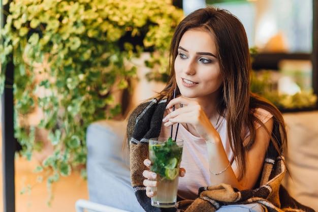 Giovane bella donna su una terrazza estiva in abbigliamento casual sta bevendo un cocktail. Foto Premium