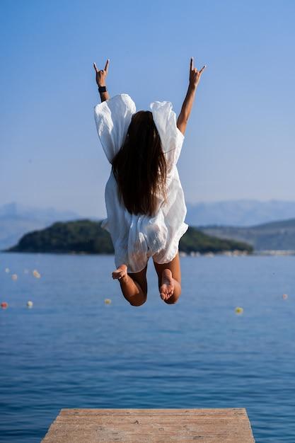 Giovane bella donna in abito bianco che salta sul molo con sfondo vista mare. il concetto di gioia, facilità e libertà durante le vacanze. la ragazza si sta godendo il resto. concetto di libertà Foto Premium