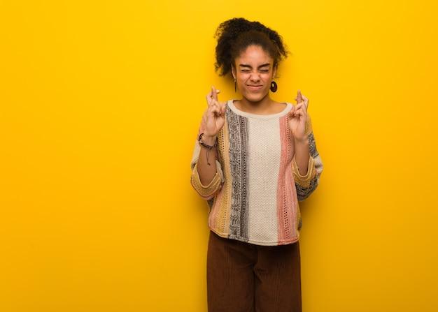 Giovane ragazza afroamericana nera con gli occhi azzurri che incrociano le dita per avere fortuna Foto Premium