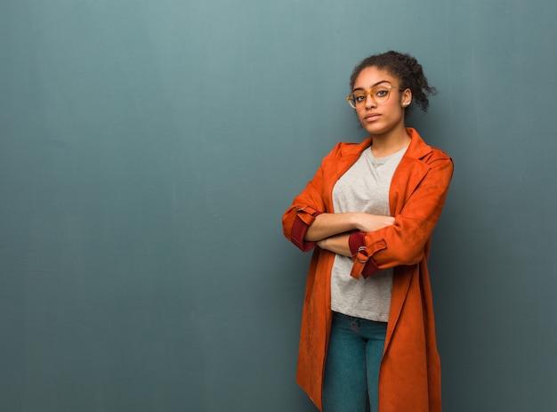 Giovane ragazza afroamericana nera con gli occhi azzurri guardando dritto Foto Premium