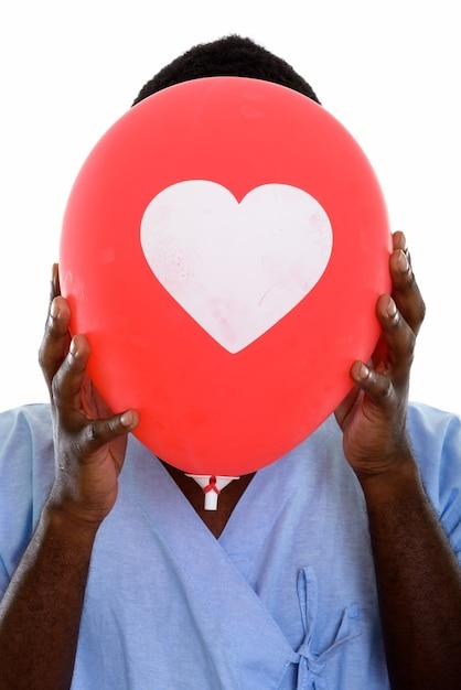 Paziente di giovane uomo africano nero nasconde il viso dietro un palloncino cuore Foto Premium