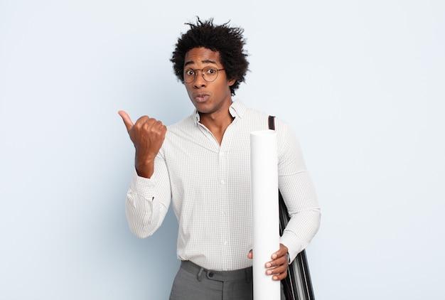 Giovane uomo afro nero che guarda stupito incredulo, indicando un oggetto sul lato e dicendo wow, incredibile Foto Premium