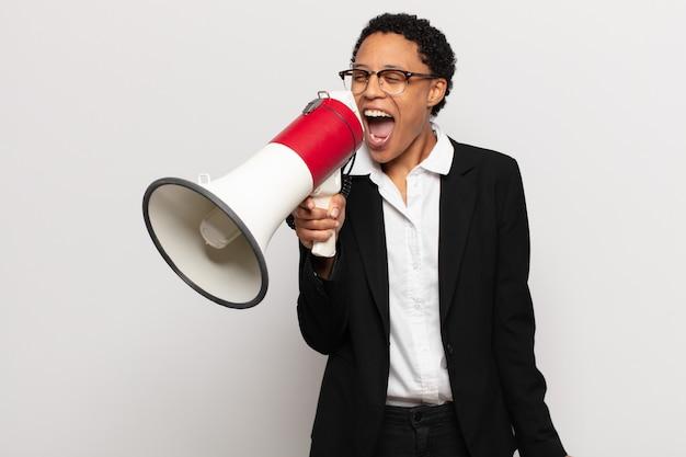 Giovane donna afro nera che grida in modo aggressivo, sembra molto arrabbiata, frustrata, indignata o infastidita, urlando no Foto Premium