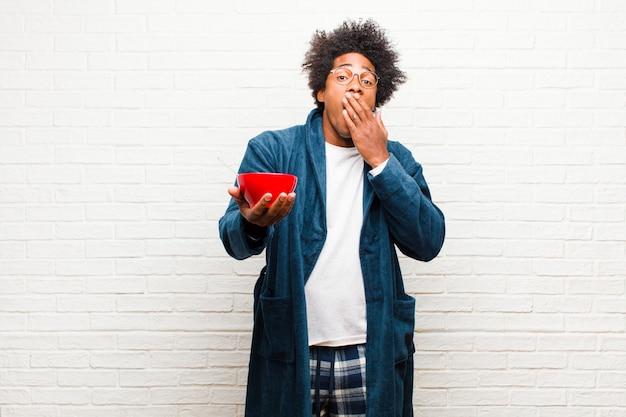 Pigiama da portare del giovane uomo di colore con una ciotola di prima colazione contro il br Foto Premium