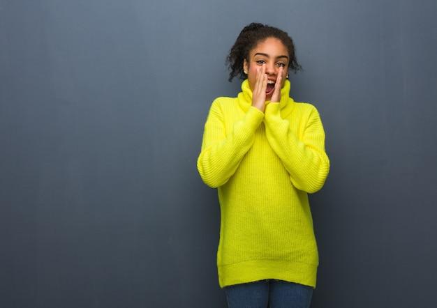 Giovane donna di colore che grida qualcosa di felice davanti Foto Premium