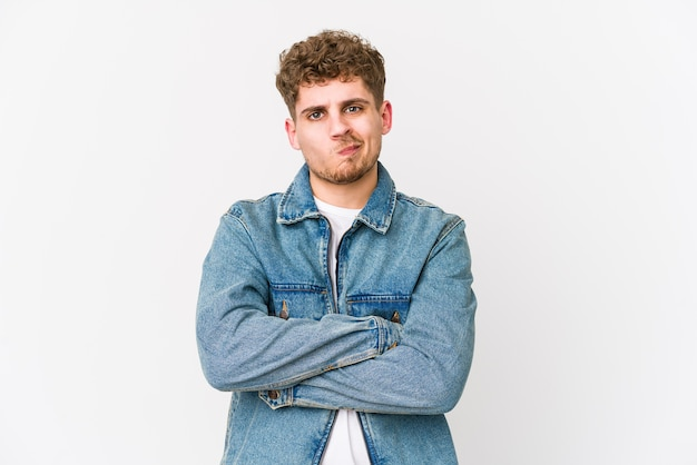 Il giovane uomo caucasico dei capelli ricci biondi ha isolato il fronte accigliato per il dispiacere, tiene le braccia conserte. Foto Premium