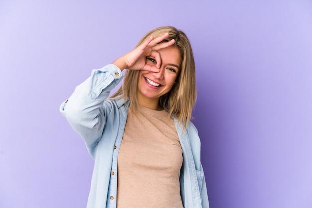 La giovane donna caucasica bionda isolata ha eccitato mantenendo il gesto giusto sull'occhio. Foto Premium