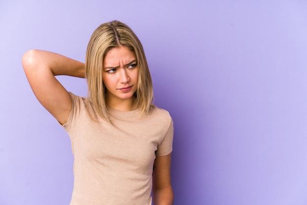 Giovane donna bionda caucasica isolata toccando la parte posteriore della testa, pensando e facendo una scelta. Foto Premium