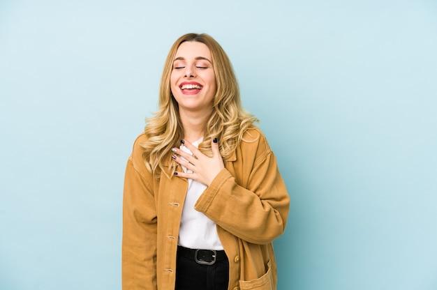 La giovane donna graziosa bionda isolata ride ad alta voce mantenendo la mano sul petto. Foto Premium