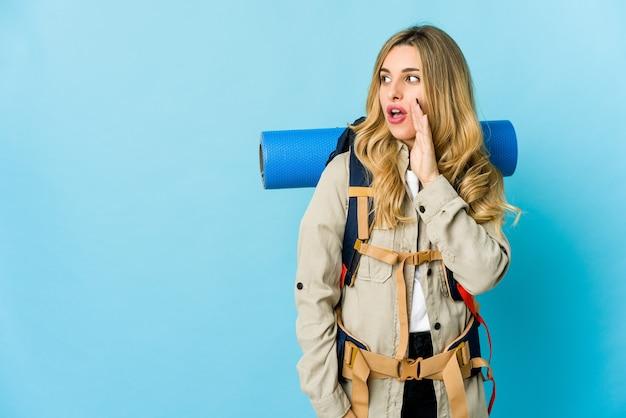 La giovane donna bionda del viaggiatore sta dicendo una notizia segreta di frenata calda e sta guardando da parte Foto Premium