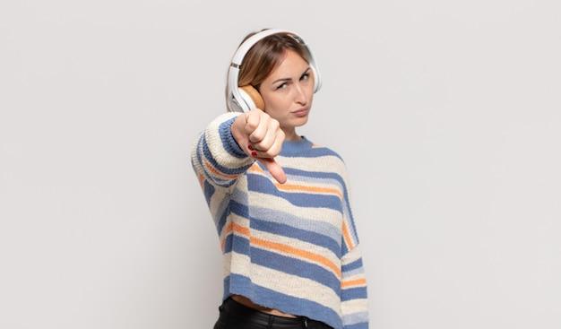 Giovane donna bionda che si sente arrabbiata, arrabbiata, infastidita, delusa o scontenta, mostrando i pollici verso il basso con uno sguardo serio Foto Premium