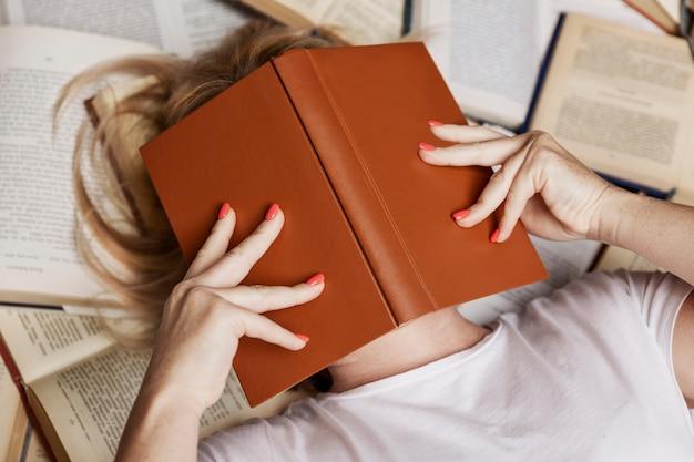 Giovane donna bionda si trova su una pila di libri che copre il viso. istruzione, conoscenza e hobby. avvicinamento. Foto Premium