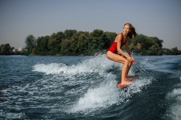 Giovane surfista biondo della donna che guida giù l'onda di spruzzatura blu Foto Premium