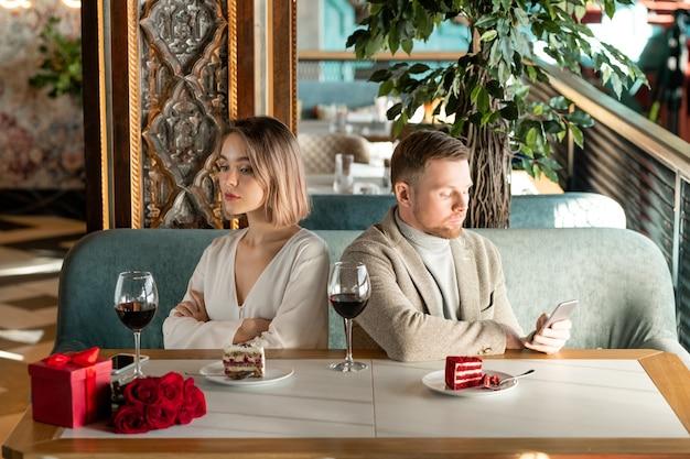 Giovane donna annoiata o offesa che si siede dalla tavola servita nel ristorante con il suo fidanzato che scorre nello smartphone nelle vicinanze Foto Premium