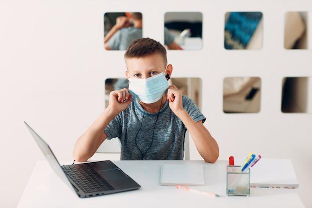 Giovane ragazzo in cuffia seduto al tavolo con laptop e maschera medica e si prepara a scuola Foto Premium