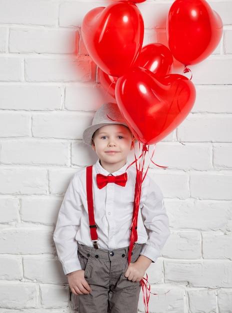 Giovane ragazzo che tiene un impulso a forma di cuore Foto Premium