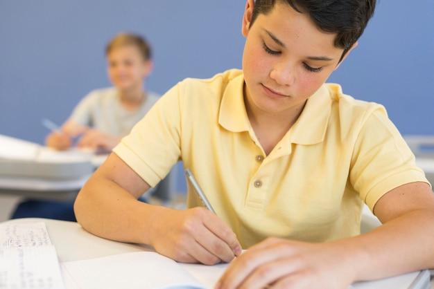Giovane ragazzo a scuola di scrittura Foto Premium