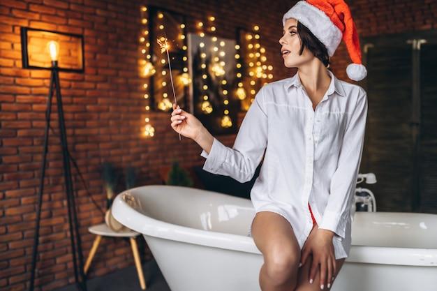 Una giovane bruna seduta sul bordo del bagno in cappello di natale che tiene la luce bengala bruciante del fuoco d'artificio sparkler nelle mani Foto Premium